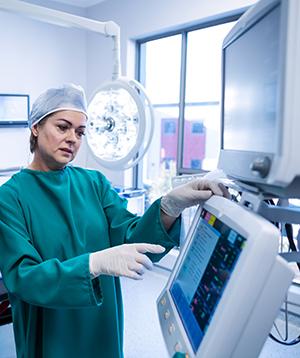 Surgeon in scrubs using a touchscreen medical computer