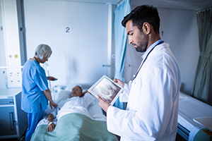 Doctor looking at medical tablet while nurse assisting a patient in hospital