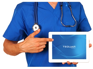 Healthcare professional holding up a Teguar tablet and pointing to the touchscreen