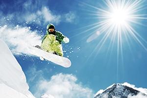 Snowboarder mid-jump under bright sunlight