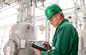 Technician in a manufacturing facility uses a rugged tablet