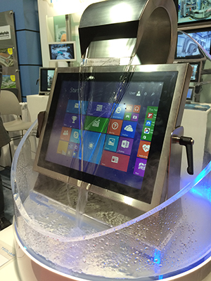 Tradeshow display of a Teguar waterproof touchscreen computer being constantly cascaded by water