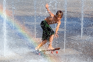Young boy skateboards through fountain with a rainbow effect