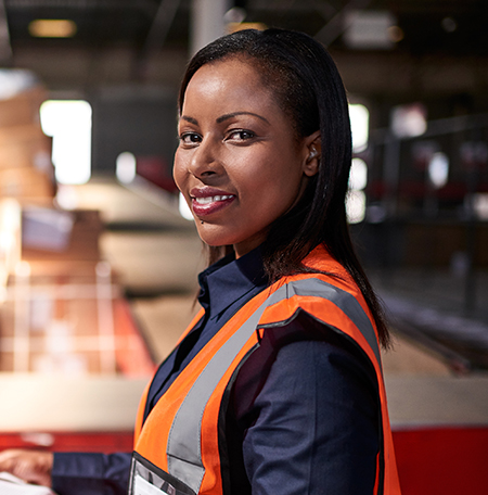 Factory engineer in a safety vest smiles